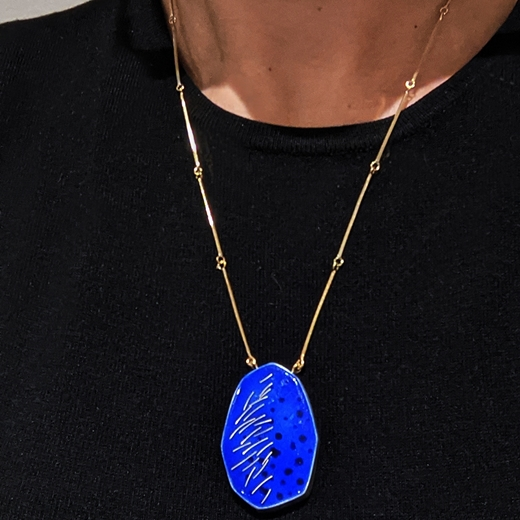 Blue and gold pendant worn