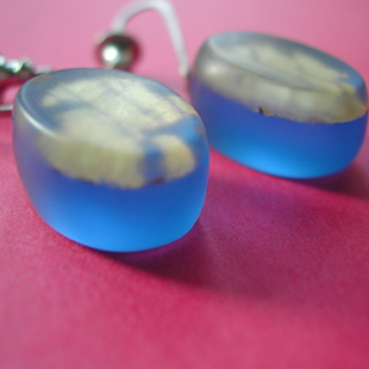 detail of blue oval drop earrings with gold leaf layer