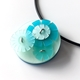Large round pale blue pendant on black rubber cord