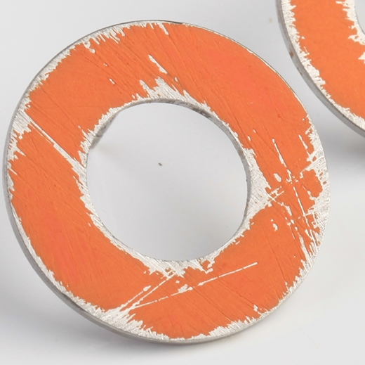 Close-up of small Orange washer earrings